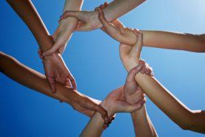Acht Hände halten sich fest